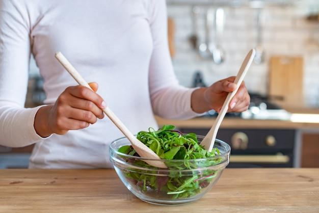Closeup mãos femininas durante o cozimento de uma comida saudável, agita com colheres uma salada