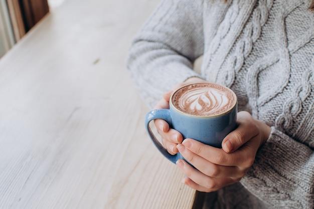 Closeup mãos femininas segurando uma xícara azul de cacau, ano novo de outono e conceito de férias
