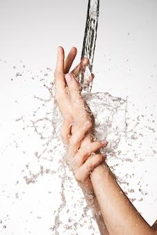 Closeup mãos femininas sob o fluxo de respingos de água - conceito de cuidados com a pele