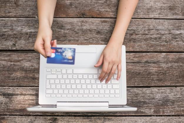 Closeup mãos jovem mão segurando cartão de crédito e usando o computador