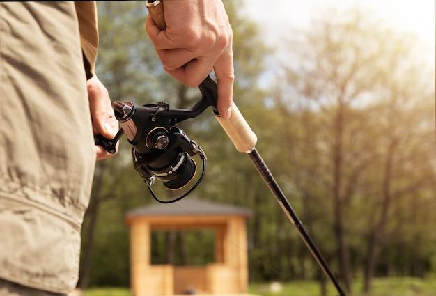Closeup mãos segurando a vara do carretel e pesca em dia de verão.