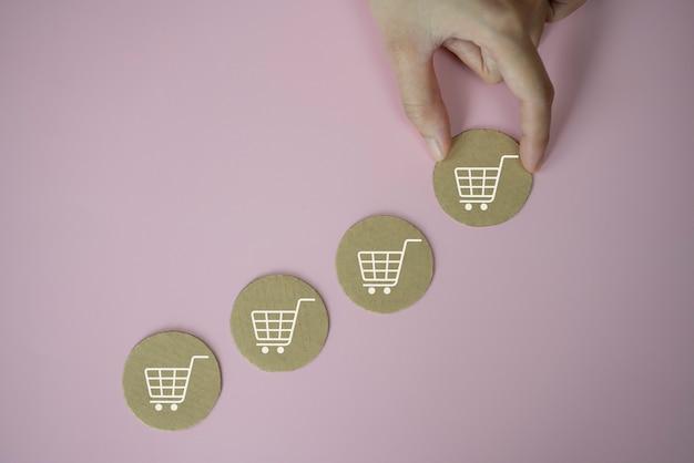 Closeup mãos segurando um ícone de papel cortado com o símbolo do ícone do carrinho de compras