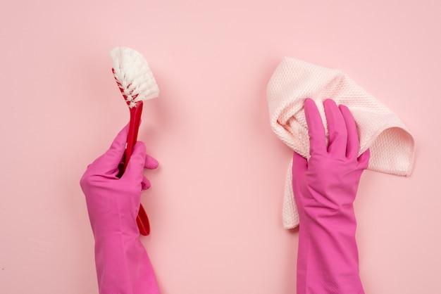 Closeup mãos vestindo luvas de látex, segurando um pano e uma escova doméstica. vista do topo