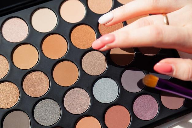 Closeup maquiagem visagiste mãos, cosméticos decorativos profissionais, paleta, conjunto de sombras e pincel.