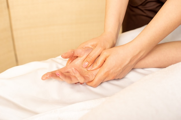 Closeup massagem de mãos femininas pelo fisioterapeuta. síndrome do túnel do carpo, artrite, conceito de doença neurológica
