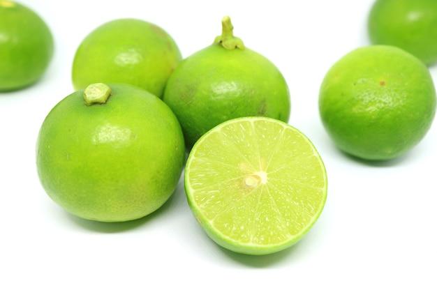 Closeup meio corte de limão verde vibrante com as frutas inteiras espalhadas no fundo branco