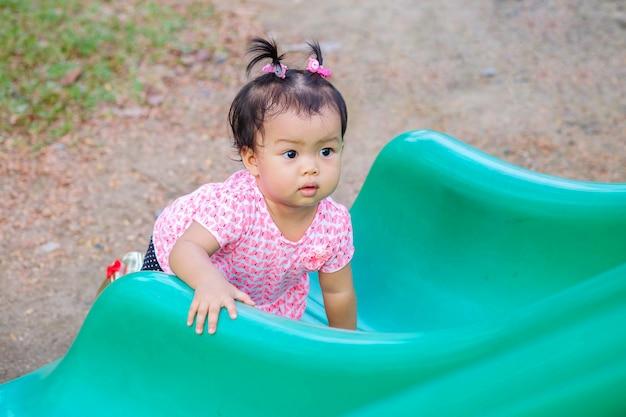 Closeup menina mentiu no controle deslizante verde no fundo do parque infantil