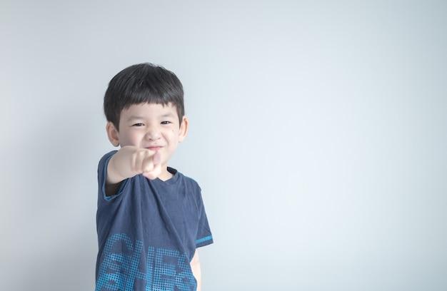 Closeup menino asiático apontando o dedo para alguém