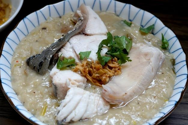 Closeup mingau de peixe pargo em uma tigela com alho frito, óleo e coentro