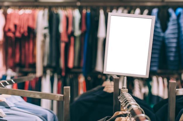 Closeup, mock up de uma tabuleta branca no fundo de uma loja com roupas.