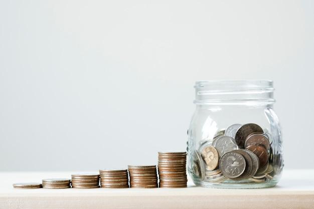 Closeup moedas empilhando gráfico para com jarra de vidro na mesa de madeira