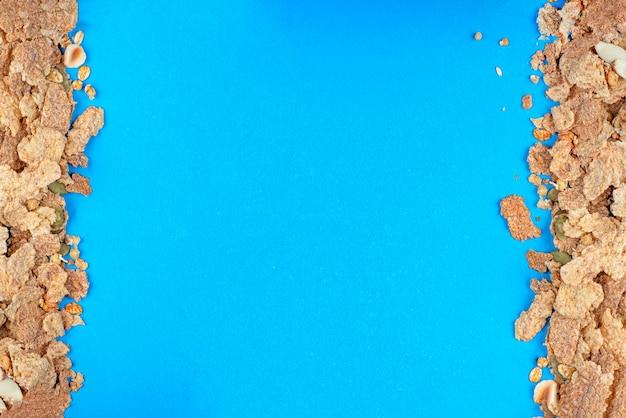Closeup muesli de muesli espalhado em uma mesa de cereais de café da manhã em um fundo azul de alimentos saudáveis ...