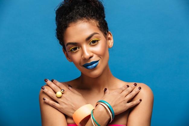 Closeup mulata nua sensual com maquiagem moda e acessórios com as mãos cruzadas no peito, parede azul