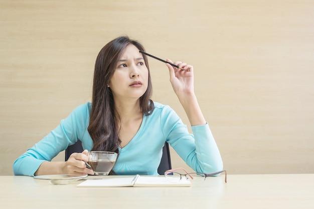 Closeup, mulher asian, trabalhando, com, pensando, rosto, e, um, lápis, e, xícara café
