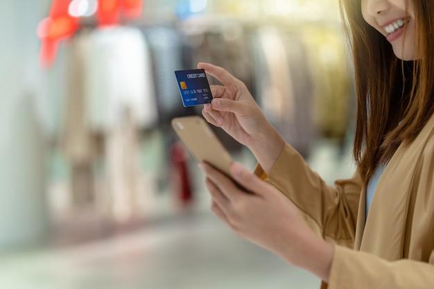 Closeup, mulher asian, usando, cartão crédito, com, móvel, para, shopping online, em, loja de departamentos