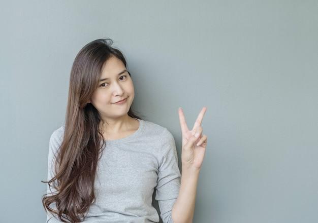 Closeup mulher asiática mantém-se dois dedos com cara de sorriso no fundo da parede de cimento turva texturizado com espaço de cópia