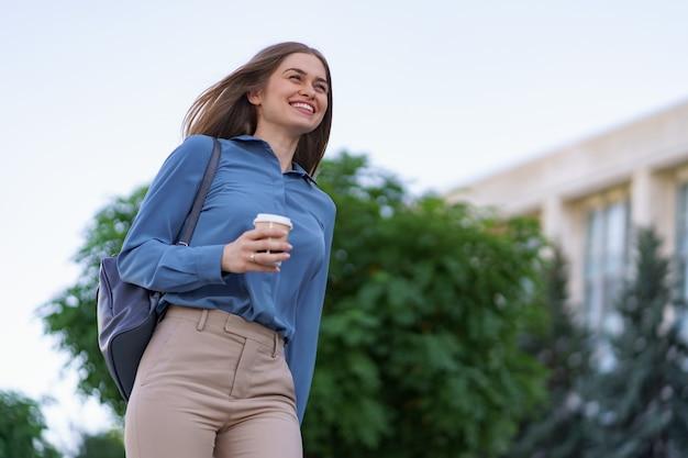 Closeup mulher atraente em movimento com café para viagem na rua da cidade. menina loira de retrato segurando um copo de papel com uma bebida quente ao ar livre.