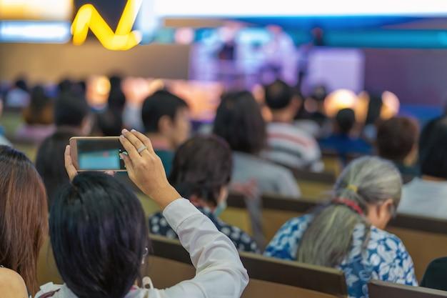 Closeup mulher audiência mão segurando o telefone móvel inteligente para tirar foto ou fazer stre ao vivo
