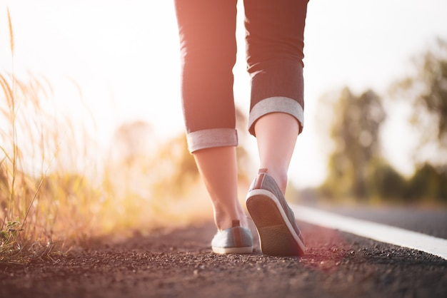 Closeup mulher caminhando em direção ao lado da estrada. conceito passo