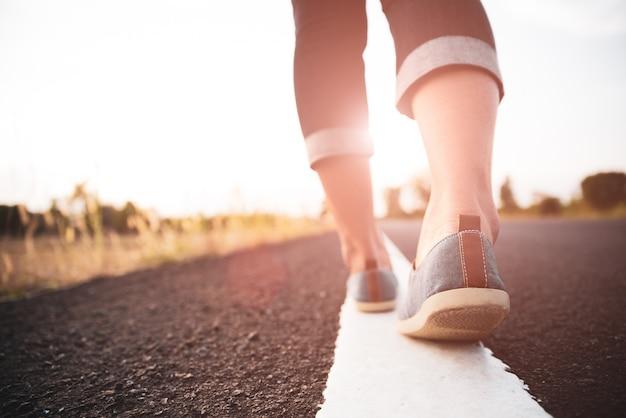 Closeup mulher caminhando em direção ao lado da estrada.