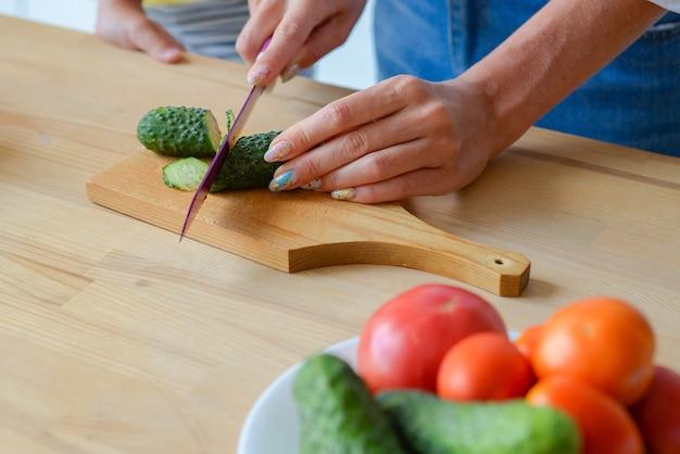 Closeup mulher com as mãos cortando pepino legumes com uma faca