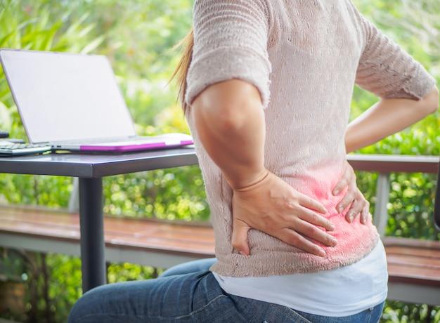 Closeup mulher com as mãos segurando a dor nas costas. síndrome de escritório e conceito de cuidados de saúde.