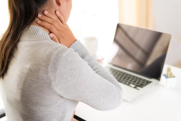 Closeup mulher com as mãos segurando a dor no ombro. síndrome de escritório