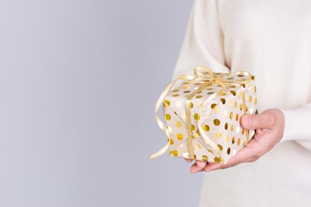 Closeup mulher entrega um presente de pacote de ouro com fita de ouro