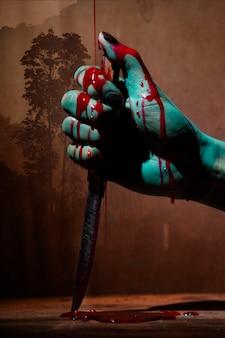 Closeup, mulher fantasma ou zumbi segurar faca para matar com violência de sangue em casa de ruína