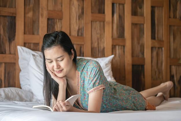 Closeup mulher lendo um livro na cama no seu quarto de manhã