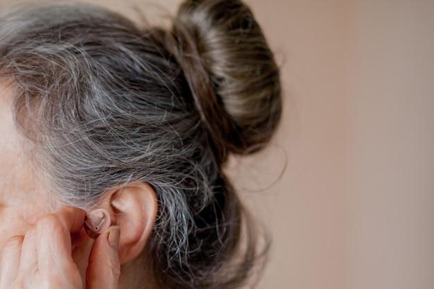 Closeup mulher sênior inserindo aparelho auditivo em seus ouvidos.
