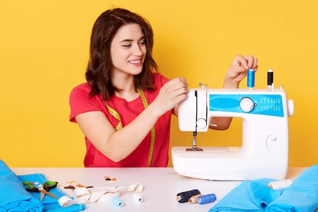 Closeup na costureira atraente, colocando a agulha na máquina de costura