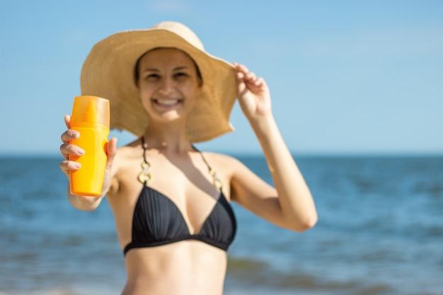 Closeup na garrafa de protetor solar na mão da mulher