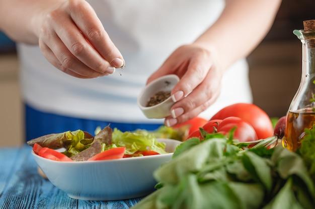 Closeup na mulher adicionando endro fresco na salada