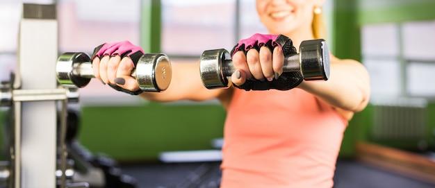Closeup na mulher fitness malhar com halteres