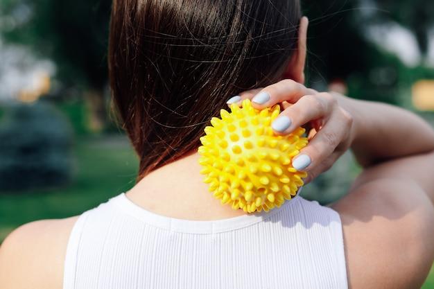 Closeup nas costas de uma jovem mulher fazendo massagem no pescoço e nos ombros com bola de borracha pontiaguda relaxante.