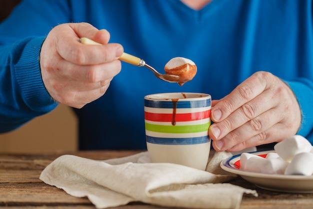 Closeup nas mãos tirando marshmallow da xícara de chocolate quente