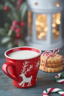Closeup no copo vermelho de leite com desenho de veado de natal, biscoitos, luzes de natal na lanterna e berry