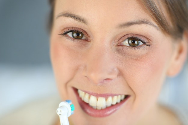 Closeup no sorriso de mulher escovando os dentes