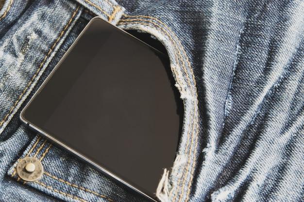 Closeup, o telefone inteligente está no bolso da frente da calça jeans azul.