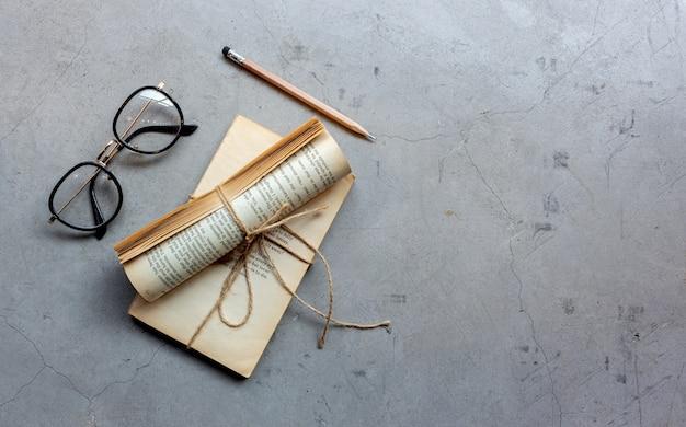 Closeup óculos, lápis e caderno no chão de cimento
