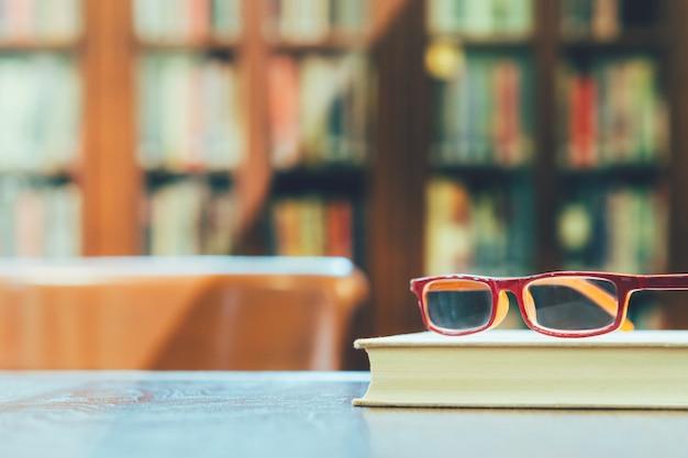 Closeup, óculos vermelhos em cima do livro de capa dura branco na mesa de madeira e cadeira na biblioteca da bela universidade com a luz do sol da tarde brilhar nas estantes de parede cheias de livro no fundo