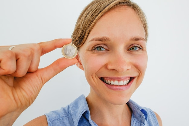 Closeup of smiling woman holding one euro coin