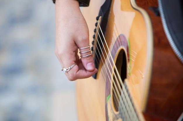 Closeup of woman playing acoustic guitar