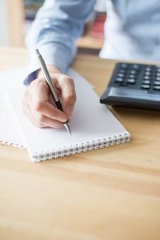 Closeup of woman using calculator and writing Foto Premium