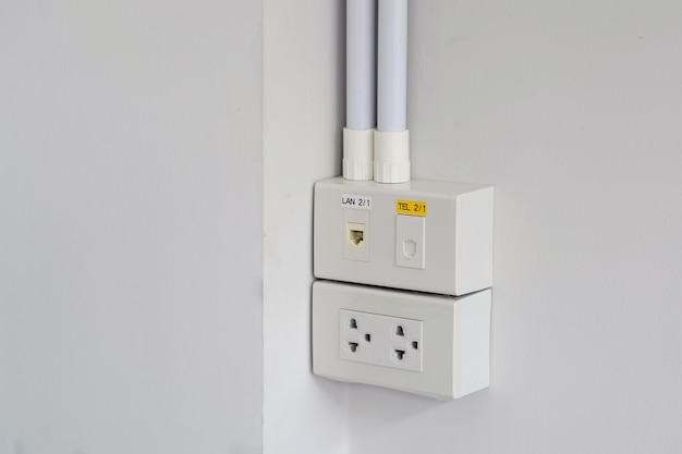 Closeup os plugues de alimentação, redes e plugues de parede de telefone para escritório e residencial.