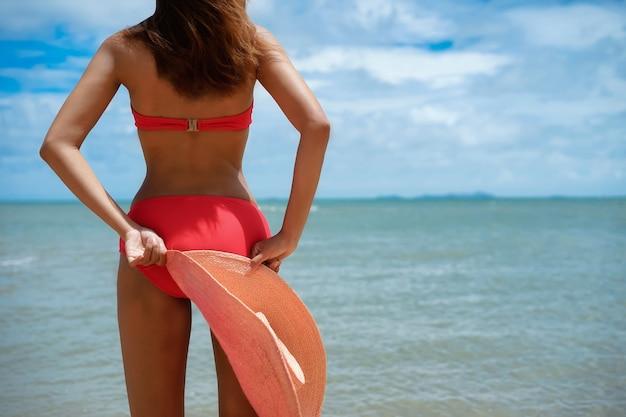 Closeup para mão de mulher segurar chapéu e feliz na praia durante as férias de verão