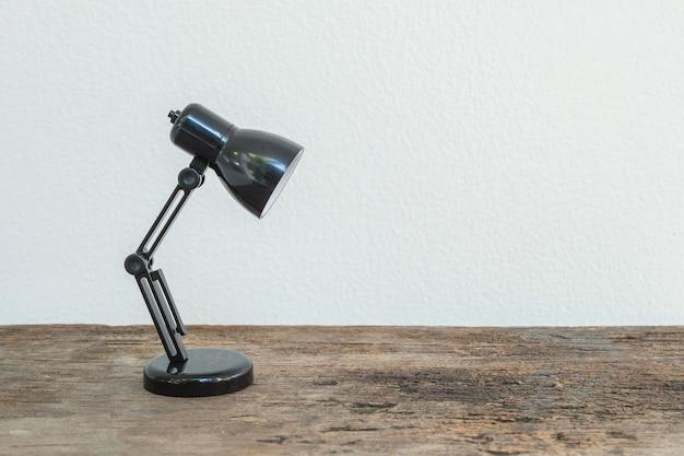 Closeup pequena lâmpada na mesa de madeira e parede de cimento branco texturizado fundo com espaço de cópia