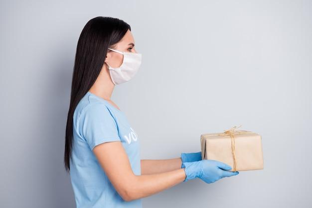 Closeup perfil vista lateral retrato dela bonita garota atraente voluntária assistente social dando caixa de papel para doação de ajuda para compra isolada sobre fundo cinza pastel
