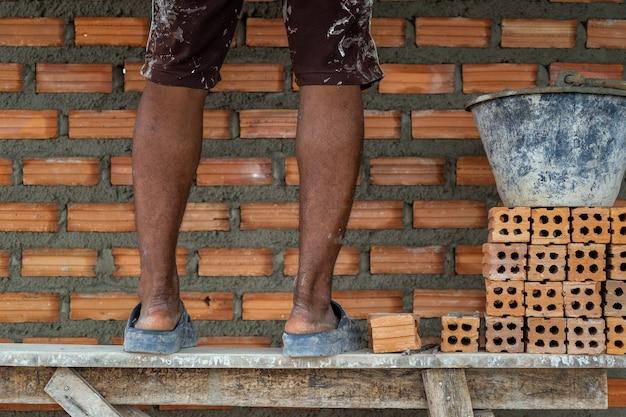 Closeup, perna, de, profissional, trabalhador construção, colocar, tijolos, em, novo, local industrial